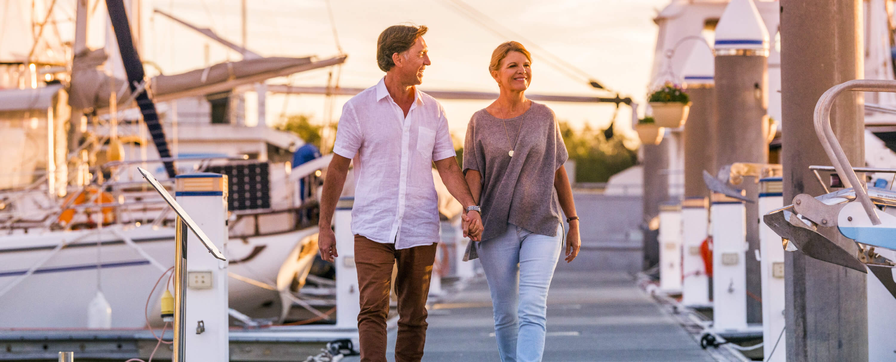 over 50s couple walking on wharf in Port Stephens